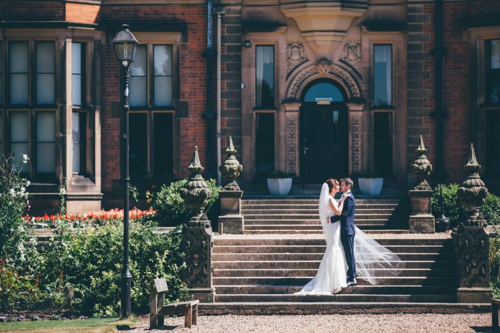 Real Bride Clare wears Jesus Peiro Dress 6005 - Bride & Groom on steps